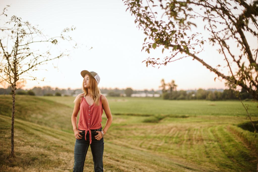 teenage girl dressed in country style clothing and hat in the field at pemberton farm weddings in snohomish wa
