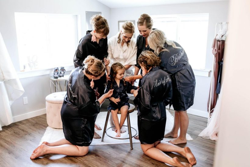 bride and bridesmaids and flowergirl getting ready in black robes getting ready in the bridal suite at pemberton farm in snohomish wa